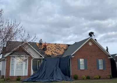 Ridgeline roofing demo shingles gray tarps brick house